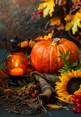 Herbst-Stillleben mit Kürbis, Sonnenblumen und brennende Kerze Standard-Bild - 62280323