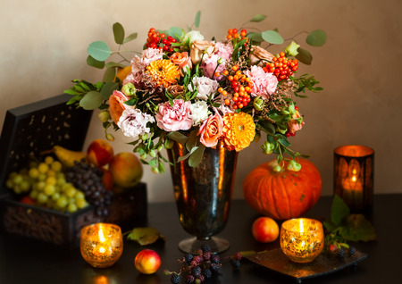 Autumn still life with flowers, pumpkin, fruits and candles Stock Photo