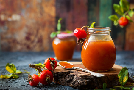 mermelada: Rose hip jam in jar with fresh berries and leaves