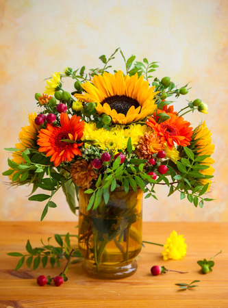autumnal flowers and berries in a vase 写真素材