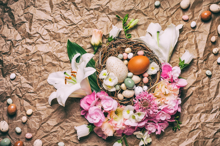 chocolate treats: Easter composition with festive flowers decoration and traditional treats : easter chocolate candy mini eggs in bird nest. Top view with copy space