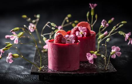 tortas de cumpleaños: tartas de mousse de frambuesa con bayas frescas y macarrones. Enfoque suave