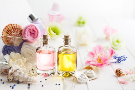 Bottles with essential aroma oil,towels different colors and fresh flowers  on white wooden background. Spa concept. Healthy cosmetic care. Place for text Stock Photo