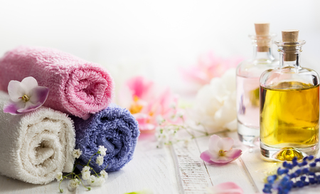 aromas: Bottles with essential aroma oil,towels different colors and fresh flowers  on white wooden background. Spa concept. Healthy cosmetic care. Place for text Stock Photo