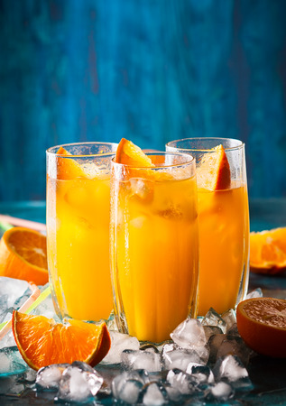 Fresh orange juice in glasses, cubes of ice and slice of fruits  on blue table. Healthy vitamin drink.