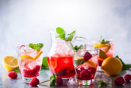 Raspberry lemonade in glasses with fresh berries and mint leaves