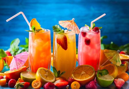 안경, 얼음 조각 및 파란색 테이블에 과일의 조각 큐브에서 여름 음료의 종류. 건강 한 비타민 과일 및 베리 음료입니다.