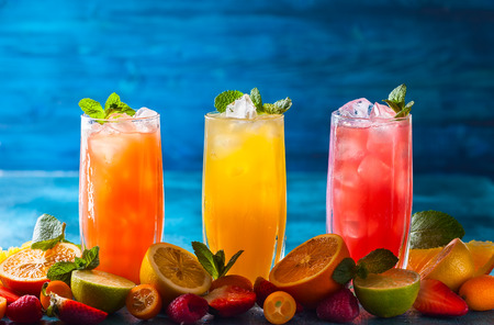 Different types of summer drinks in glasses, cubes of ice and slice of fruits  on blue table. Healthy vitamin fruit and berry drinks. Banco de Imagens - 76772115