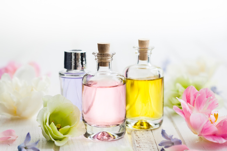 Bottles with essential aroma oil and flowers on white wooden background. Healthy skin care. Place for text. Imagens