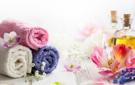 spa flower: Bottles with essential aroma oil,towels different colors and fresh flowers  on white wooden background. Spa concept. Healthy cosmetic care. Place for text Stock Photo