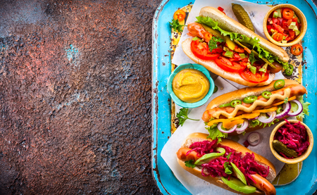 Variety of delicious hot dogs with vegetables and sauces on a vintage serving tray. View from above.