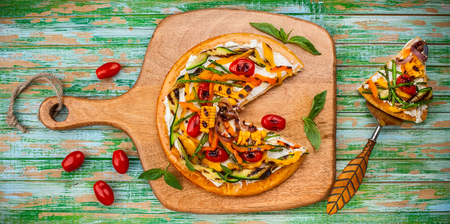 Delicious summer appetizer: Vegetarian pizza with grilled vegetables and soft cheese on wooden board. Top view