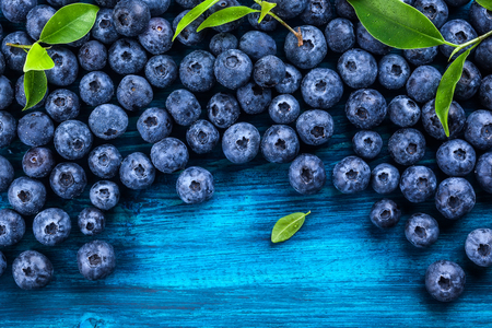 Fresh blueberry with drops of water on blue wooden background. Top view. Concept of healthy and dieting eating