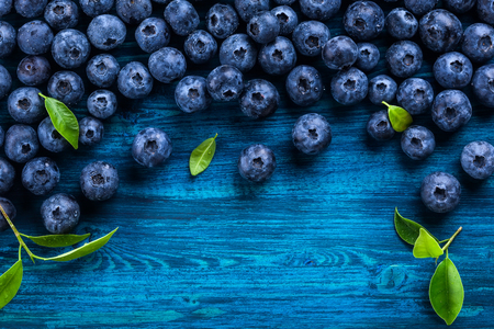 wildberry: Fresh blueberry with drops of water on blue wooden background. Top view. Concept of healthy and dieting eating