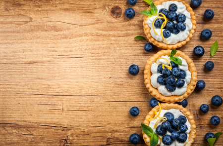 Delicious Blueberry tartlets with vanilla cream on the wooden background. Top view. Imagens