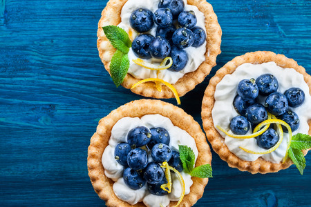 wildberry: Delicious Blueberry tartlets with vanilla cream on  blue wooden background. Top view.