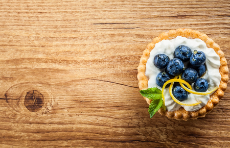 Delicious Blueberry tartlets with vanilla cream on the wooden background. Top view. Stock fotó