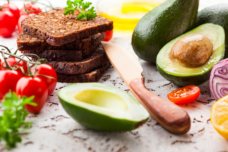 Fresh ingredients for making healthy vegetarian sandwiches with black bread,avocado and tomatoes. Concept healthy eating. Stock Photo