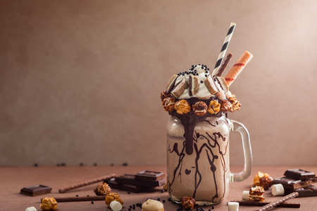 Chocolate  milkshake with ice cream and with whipped cream, marshmallow, sweet popcorn, cookies, waffles, served in glass mason jar. Freak or crazy sweet shake. Imagens