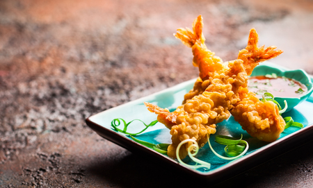Shrimps tempura with spicy chili sauce on blue plate.  Seafood tempura dish of traditional asian cuisine . Stock Photo - 79041516
