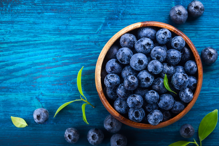 wildberry: Fresh blueberry with drops of water in wooden bowl on blue  background. Top view. Concept of healthy and dieting eating Stock Photo