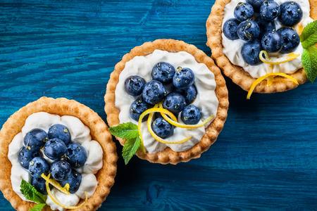 Leckere Blaubeertörtchen mit Vanillecreme auf blauem Holzhintergrund. Draufsicht