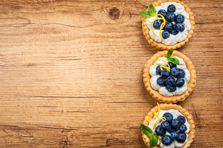 wildberry: Delicious Blueberry tartlets with vanilla cream on the wooden background. Top view. Stock Photo