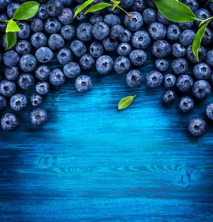 おいしいブルーベリーのタルト バニラ クリームに木製の背景を持つ。平面図です。