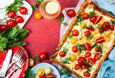 Deliciously simple tomato tart made with puff pastry, red and yellow cherry tomatoes, spinach and ricotta cheese. The perfect appetizer for summer. Concept of healthy eating or vegetarian food on red rustic wooden background, top view.