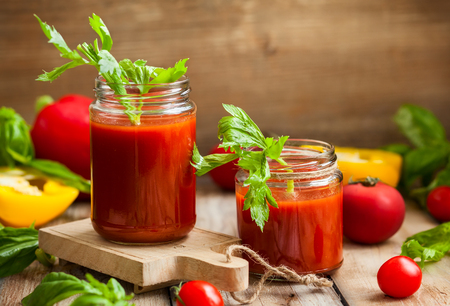 Spicy tomato drink with celery and pepper. Tomato drink in jar surrounded of fresh vegetables on a wooden table