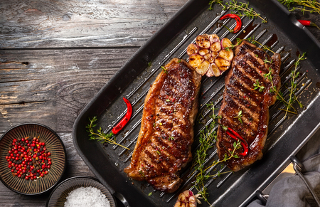 Grilled  striploin steak with spices and herbs on grill iron pan.The strip steak, also called a New York strip. Stock Photo