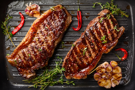 Grilled  striploin steak with spices and herbs on grill iron pan.The strip steak, also called a New York strip. Zdjęcie Seryjne