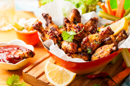 Delicious barbecue chicken wings with two sauces and carrot with celery in vintage serving bowl. Archivio Fotografico