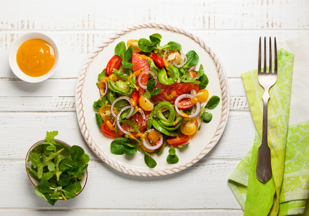 mustard leaf: Smoked salmon, avocado and cherry tomatoes salad with honey mustard dressing.Healthy salad in a plate on a wooden table. Top view Stock Photo
