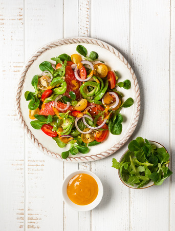 Smoked salmon, avocado and cherry tomatoes salad with honey mustard dressing.Healthy salad in a plate on a wooden table. Top view Stock Photo