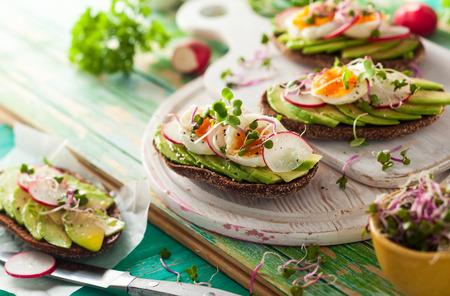whole wheat toast: Open sandwiches with avocado,radish, boiled egg and sprouts. Concept of healthy eating or vegetarian food.