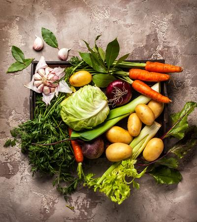 Verscheidenheid van verse rauwe plantaardige ingrediënten voor het koken van groentesoep of stoofpot. Het plantaardige stilleven van de herfst op rustieke uitstekende achtergrond. Bovenaanzicht