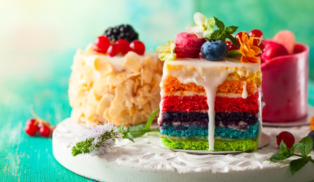 Various slices of cakes on a white tray: rainbow cake, raspberry cake and almond cake. Sweets decorated with fresh berries and flowers for holiday Stockfoto