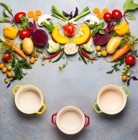 Concept of cooking healthy eating. Still life with fresh vegetables and mini pots for cooking. Top view. Stock Photo