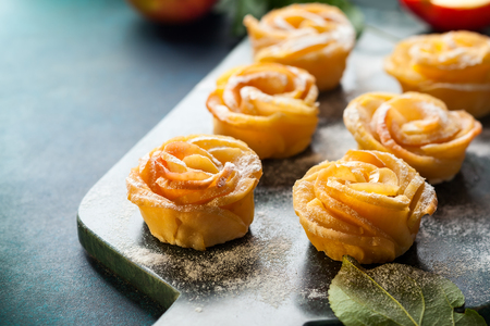 Apple Rose mini tarts with icing sugar on the stone cutting board. Imagens