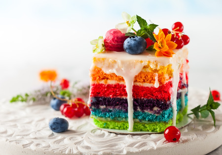 A slice of rainbow cake decorated with fresh berries and flowers for holiday Reklamní fotografie