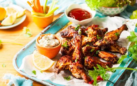 Heerlijke barbecue kippenvleugels met twee sauzen en wortel met selderij op vintage dienblad.