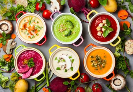 Verscheidenheid van kleurrijke groentensoepjes en ingrediënten voor soep. Bovenaanzicht. Concept van gezond eten of vegetarisch eten.
