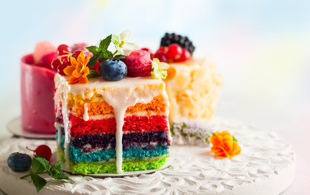 Various slices of cakes on a white tray: rainbow cake, raspberry cake and almond cake. Sweets decorated with fresh berries and flowers for holiday Imagens