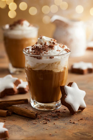 Two glasses of coffee shake with whipped cream, chocolate and winter spices for Christmas