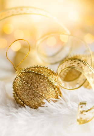 Gold Christmas baubles on white fur with gold sparkling background. Festive winter concept.