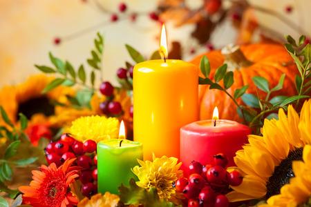 Herfst concept met kleurrijke kaarsen en bloemen branden Stockfoto