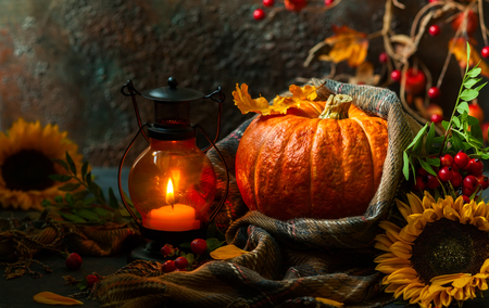 Autumn still life with pumpkin, sunflowers and burning candle