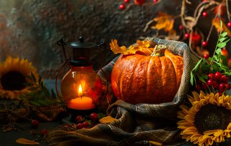Herbststillleben mit Kürbis, Sonnenblumen und brennender Kerze Standard-Bild - 85093576