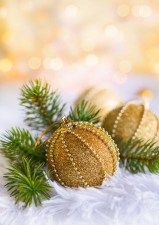 Gold Christmas baubles on white fur with gold sparkling background. Festive winter concept. Stock Photo